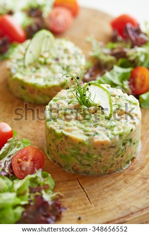 two portions of salad with salmon and avocado decorated with a slice of lime and stems - stock photo
