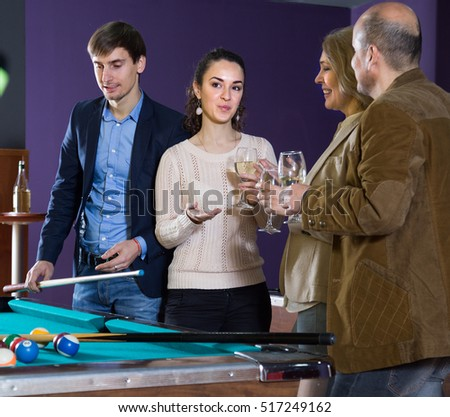 two positive adult couples of different generations are drinking wine in the billiard room. focus on girl