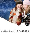 Two positive beautiful girls with great gesture in winter decoration with clear space - stock photo