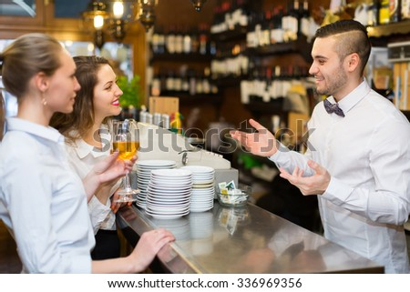 Two positive female friends chatting and drinking wine in bar  - stock photo