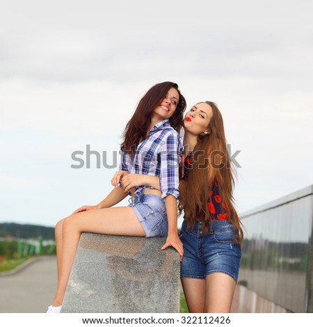 Two positive hipster girlfriends. Friends girls communicate outdoors in the city.