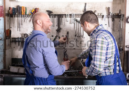 Two positive mechanics working at workshop  - stock photo