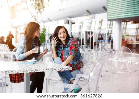 Two positive young girls laughing, hanging out in a cafe. Modern interior with transparent chairs.  - stock photo