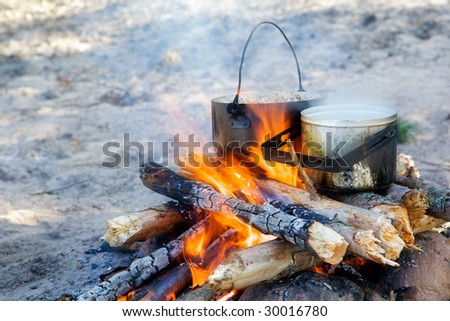 Two pot with food on a bonfire. - stock photo