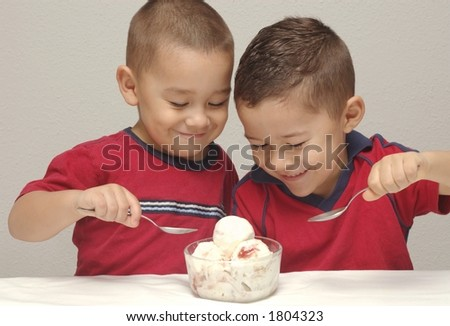 Two preschool brothers prepare to enjoy a large bowl of strawberry-cheesecake  ice cream - stock photo