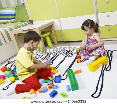 Two preschool children build castles with plastic cubes - stock photo