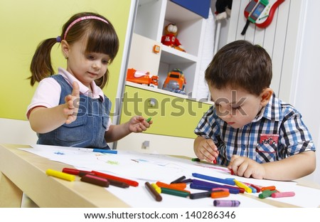 Two preschool children draw with crayons - stock photo