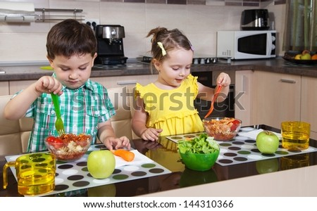 Two preschool children who eat healthy food in the kitchen - stock photo