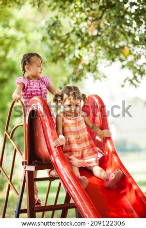 Two preschool girls on the slide at the playground - stock photo