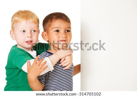 Two preschooler boys holding a blank placard - stock photo