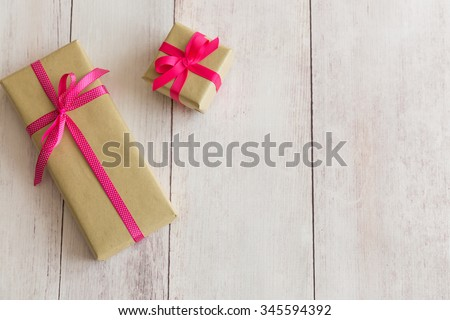 Two presents gifts boxes with brown wrapping paper and pink and pink and white polka dot ribbons on off white wooden background - stock photo