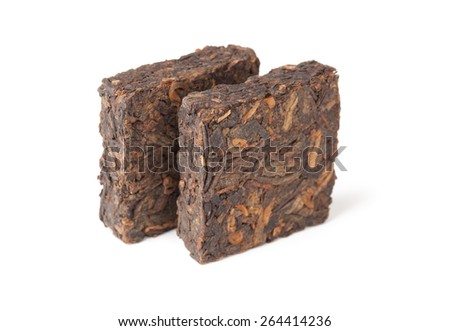 Two pressing briquette of black Chinese Shu Pu Erh tea stand isolated on white background, selective focus, shallow DOF - stock photo