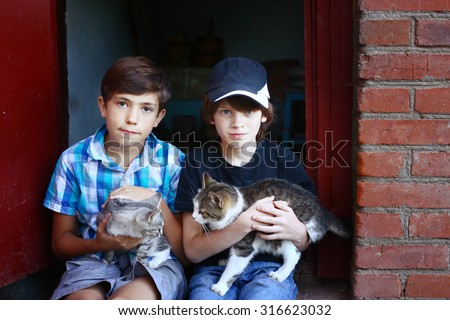 two preteen boys with cats on knees sit on the house porch - stock photo