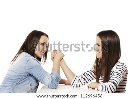 two pretty arm wrestling teenager on white background - stock photo