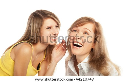 Two pretty blond girls whispering about their secrets; isolated on white background - stock photo