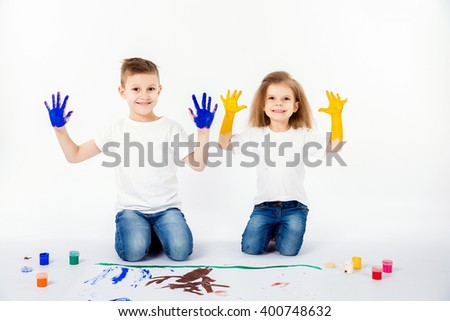 Two pretty child friends boy and girl in white shirts and blue jeans, trendy hair style, barefoot, drawing on white sheet of paper isolated. Showing hands in paint, roar, happy. - stock photo
