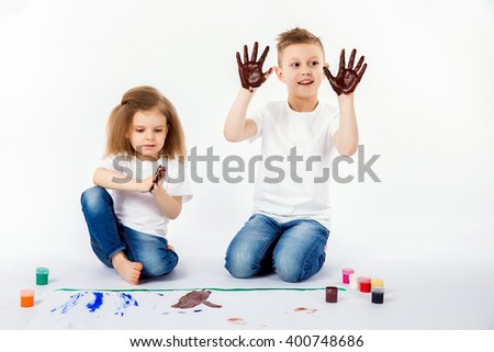 Two pretty child friends boy and girl in white shirts and blue jeans, trendy hair style, barefoot, drawing on white sheet of paper isolated. Showing hands in paint, roar, happy.