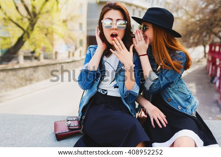 Two  pretty cuter teenagers  shares secrets, gossip. Surprise face, emotions,  Best friends wearing stylish outfit, black hat, sunglasses, dress. Bright spring  colors.  - stock photo