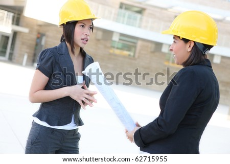 Two pretty diverse women architects on construction building site - stock photo