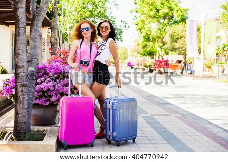 Two pretty fashionable happy girl with a suitcase waiting in the terminal at the airport. Red-haired, brunette, dressed in shorts and a bright T-shirt, sunglasses. - stock photo