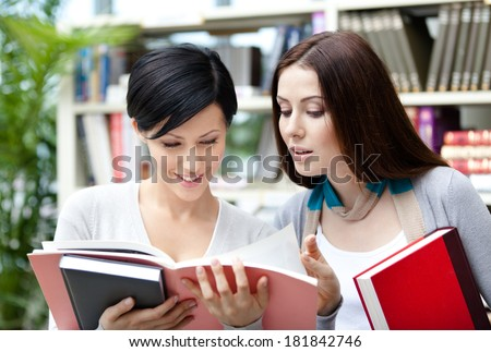Two pretty female students read books at the library - stock photo