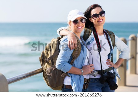 two pretty female tourists standing on beach pier - stock photo
