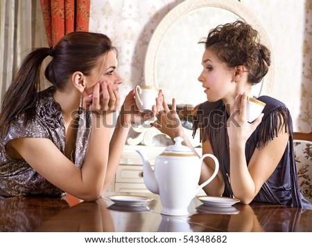 Two pretty girl-friends talk and drink tea in drawing room - stock photo