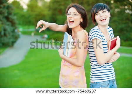 Two pretty girl-student in a park holding a book one of them shows the forward - stock photo