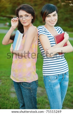 Two pretty girl-student in the park are holding books on natural background - stock photo