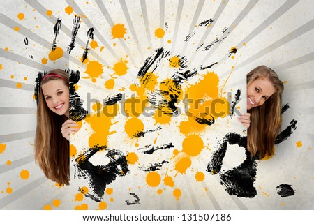 Two pretty girls holding abstract art of yellow ink and black handprints - stock photo