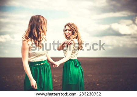 Two pretty girls holding hands in the brown field - stock photo