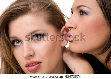Two pretty girls sharing a secret - stock photo
