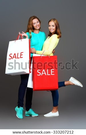 Two pretty girls standing with shopping bags and smiling happily. Beauty, fashion. Sale, shopping concept. - stock photo