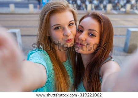 Two pretty girls taking selfie. Urban background. We love selfie photo. - stock photo