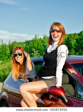 Two pretty happy girls in the car. Concept of carefree roadtrip - stock photo