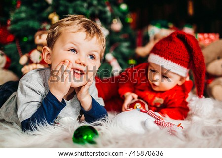 Two pretty little boys lie on fluffy carpet before a Christmas tree