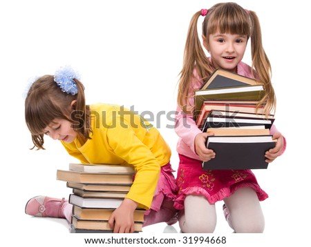 Two pretty little girls holding stack of books - stock photo