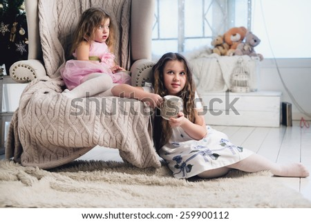 Two pretty little sisters sitting on sofa - stock photo