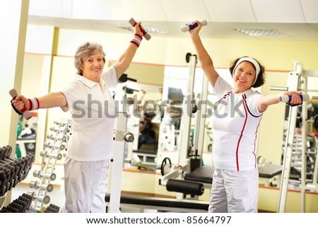 Two pretty senior women exercising with dumbbells - stock photo