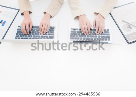 Two Pretty Smiling Businesswomen Discussing the Business using Laptop Device. - stock photo