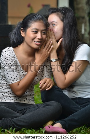 Two pretty southeast asian girls sharing exciting secret stories / gossiping  with happy expression at outdoor scene - stock photo
