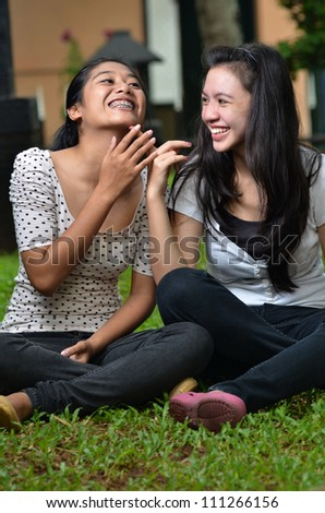 Two pretty southeast asian girls sharing exciting stories / gossiping  with happy expression at outdoor scene - stock photo