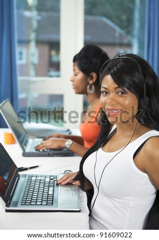 Two pretty students doing project work on laptops with one young lady looking up and smiling - stock photo