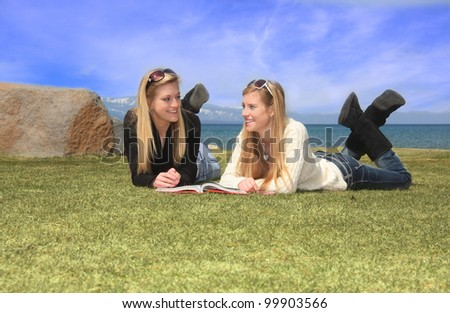 Two pretty teen aged girls laying on grass in front of a lake, studying from a book. - stock photo