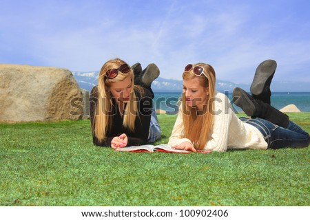Two pretty teen girls laying on a grassy park area studying a book. - stock photo