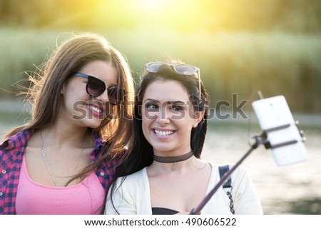 Two pretty teenage girls taking selfie on mobile phone with stick in the nature beside river. Positive emotions