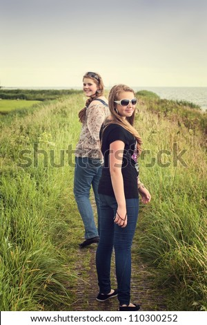 Two pretty teenagers walking on a dike - stock photo