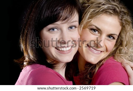 Two Pretty woman friends in pink hugging