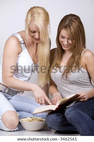 two pretty womem on grey background reading book