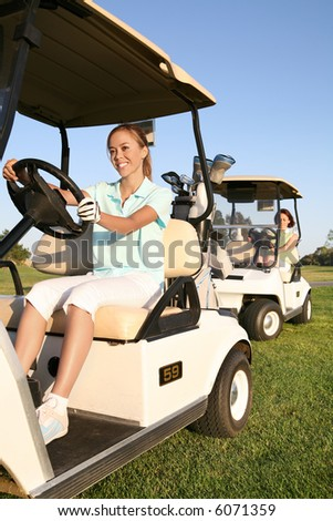 Two pretty women golfers driving in the golf carts - stock photo